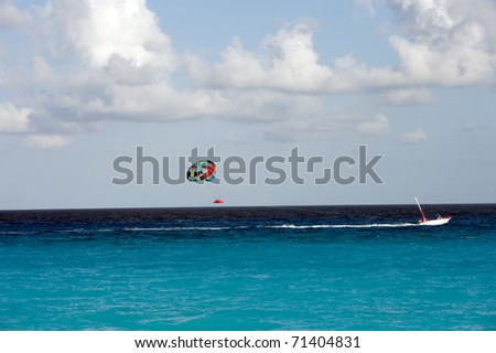 parasailing in the ocean off of Cancun Mexico - stock photo