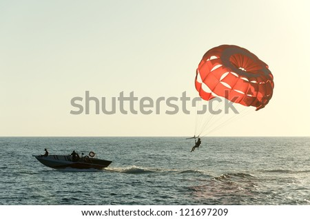 Parasailing on a red parachute over water