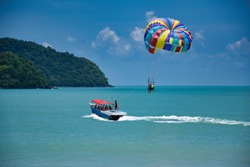 Parasailing on the waves of the azure Andaman sea under the blue sky near the shores of the sandy beautiful exotic and stunning Cenang beach in Langkawi island, in Malaysia