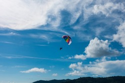 Parasailing, or parascending or para kiting, a recreational kiting activity, flying in the clear blue sky. In Patong beach, Phuket, Thailand.