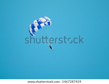 Parasailing. Skydiver on parachute flies in the sky after the boat. Active lifestyle. Extreme sport.  #1467287459