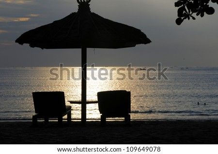 Parasol and chairs on Bali beach at sunset - stock photo
