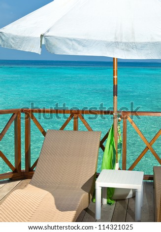Parasol and chaise lounge on a terrace of water villa, Maldives