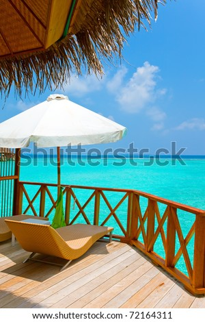 Parasol and chaise lounges on a terrace of water villa, Maldives. #72164311