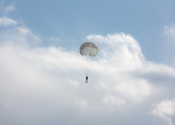 Paratrooper in the sky with a parachute in flippers