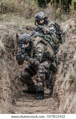 Paratroopers of french 1st Marine Infantry Parachute Regiment RPIMA in entrenchments, pointing to camera front view