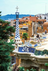 Parc Guell, visitors on a viewpoint with unusual architectural style, cityscape of Barcelona on the background, Spain