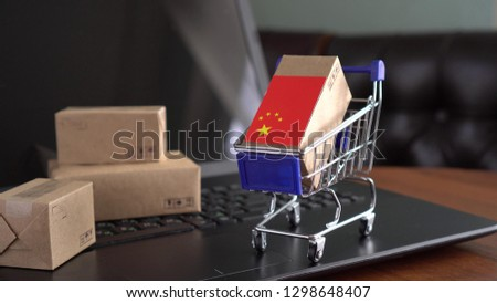 Parcel Boxes with a flag of China in a shopping cart on a laptop keyboard. International Trade in Goods and Services by Country