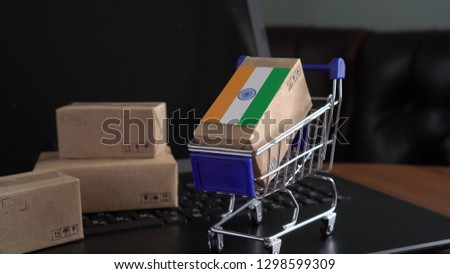Parcel Boxes with a flag of India in a shopping cart on a laptop keyboard. International Trade in Goods and Services by Country