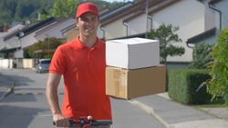 Parcel delivery man skilfully holds two boxes in one hand while riding an electric scooter. Content young courier rides his e-scooter down the empty suburban street with two packages.