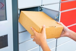 Parcel delivery, pickup point with lockers, hand with parcel, contactless pack delivery
