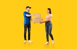 Parcel Delivery. Woman Receiving Boxes From Male Courier Standing Over Yellow Studio Background. Post Package Delivering And Transportation, Couriers Service Concept. Full Length
