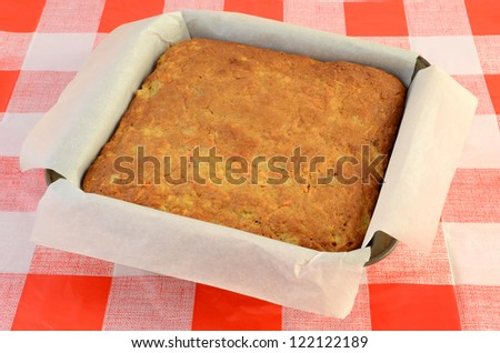 Parchment lined cake pan with cooked carrot cake cooling on red and white checked cloth