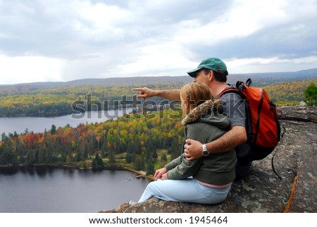 Parent and child sitting on cliff edge enjoying scenic view