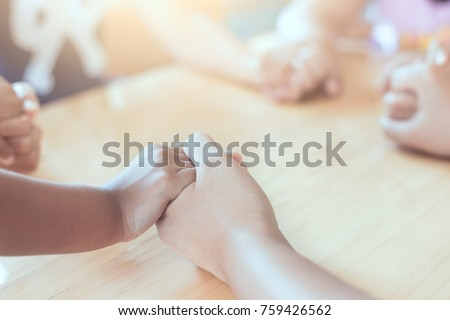 Parent and children holding hands and praying together on wooden table #759426562
