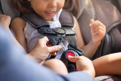 Parent buckling her child's seat belt in the car. Transportation safety.