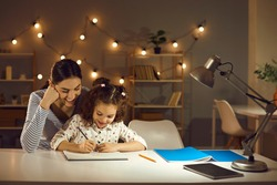 Parent helping child. Happy family doing homework in the evening. Mother and daughter working on school assignment sitting at desk with lamp in cozy dark room with LED lights. Kids learning concept