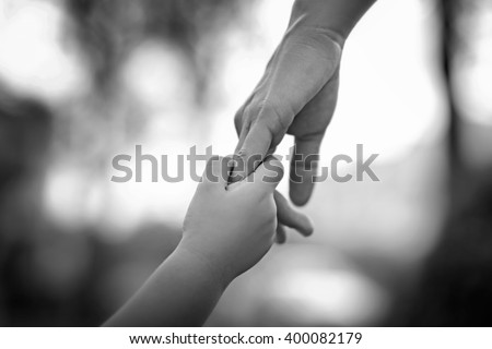 Parent holds the hand of a little child on abstract blur background, soft focus, black and white tone