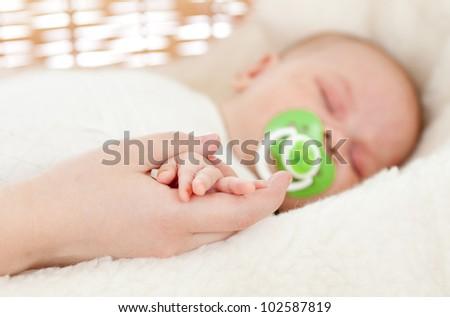 parent's hand keeping newborn baby's one