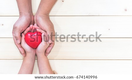 Parent supporting child's hands with red heart for I love you dad, Father's Day holiday celebration, and home family nursing for kids health care concept #674140996