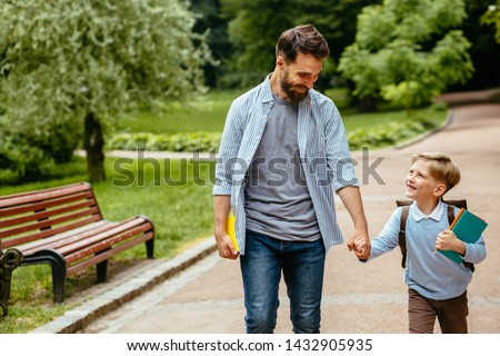 Parent take child to school. Pupil of primary school go study with backpack outdoors. Father and son go hand in hand. Beginning of lessons. Back to school. First day of fall. Elementary student.