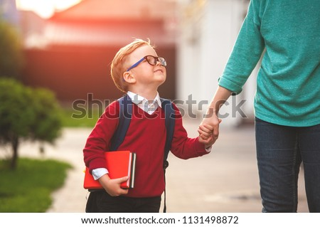 Parent take child to school. Pupil of primary school go study with backpack outdoors. Mother and son go hand in hand. Beginning of lessons. Back to school. First day of fall. Elementary student. #1131498872