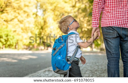Parent taking child to school. Pupil of primary school go study with backpack outdoors. Father and son go hand in hand. Beginning of lessons. Back to school. First day of fall. Elementary student.