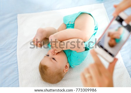 Parent taking photo of a baby with smartphone. Adorable newborn child taking foot in mouth. sucking feet. Digital family memories