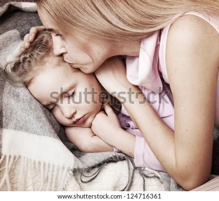 Parent touching forehead sleeping child. Illness child