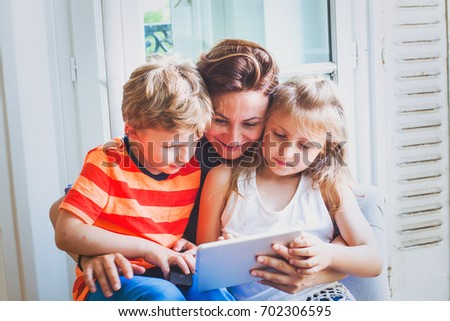 parent with children learning computer tablet, mother with two kids watching something on the screen of device