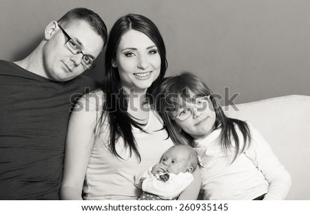 Parenthood and happiness concept. Young family mother father and child preschooler sitting on sofa with newborn baby girl at home. Black & white