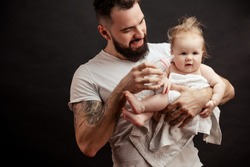 Parenting and love concept. Father holding and taking care of little infant one-year old baby, feeding or watering from nursing bottle.