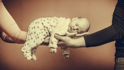 Parenting family and love concept. one month old baby girl sleeping in the comfort of parents arms, vintage filter