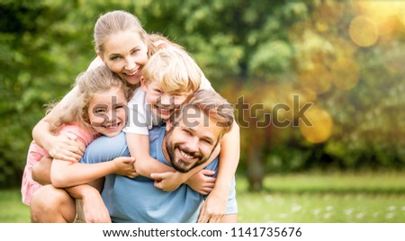 Parents and children as happy family hugging in spring