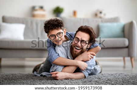 Parents and children being friends. Joyful father and son having fun, dad lying on floor, carrying boy on back and smiling together to camera, spending tim at home together. Single dad concept