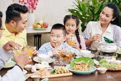 Parents and children drinking juice and eating traditional Vietnamese dishes at family dinner