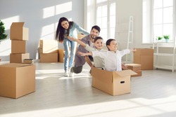 Parents and children moving in. Husband and wife with their children, who are sitting in a cardboard box having fun in their new home. Concept of buying your own home and moving.