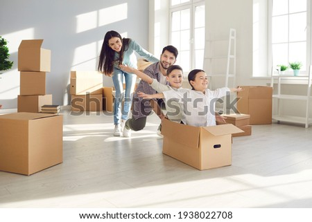 Parents and children moving in. Husband and wife with their children, who are sitting in a cardboard box having fun in their new home. Concept of buying your own home and moving. Stock foto ©