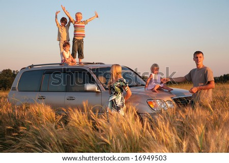 Parents and children on offroad car on wheaten field