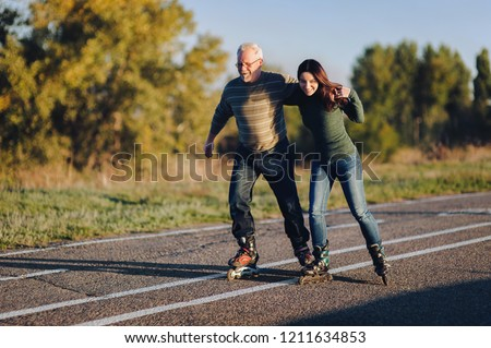 Parents and children spend time together. Older generation and sport. Active lifestyle of the pensioner. Happy old man riding on rollers with his daughter on the road in autumn park.