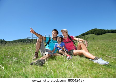 Parents and kid on a hiking day in mountain