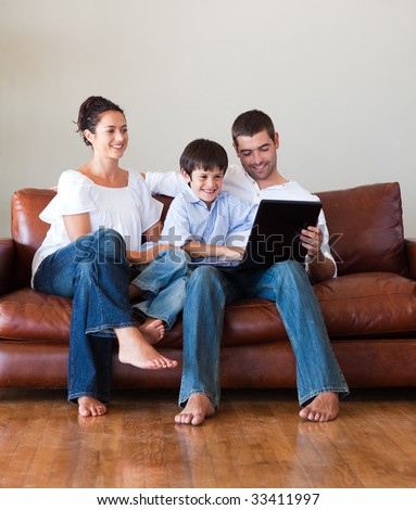 Parents and kid playing with a laptop on a couch at home