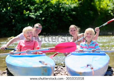 Parents and kids kayaking on the river. Active happy family, father, mother and two teenage school boys, having fun together enjoying adventurous experience on a sunny day during summer vacation.