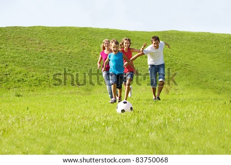Parents and kids running to the ball