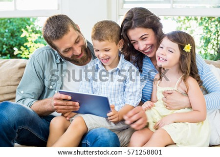 Parents and kids using digital tablet in living at home