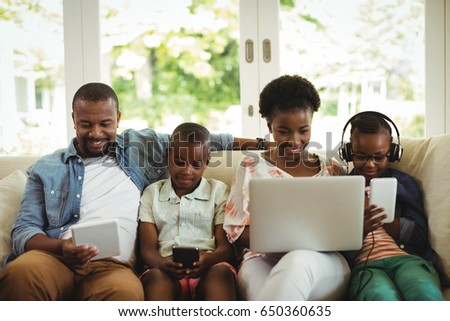 Parents and kids using laptop, smartphone and digital tablet on sofa at home