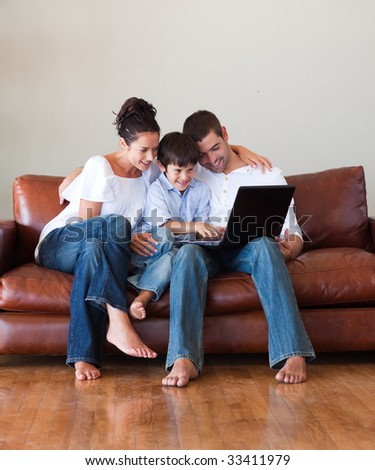 Parents and son playing with a laptop at home