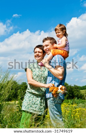 Parents and their daughter standing in the meadow