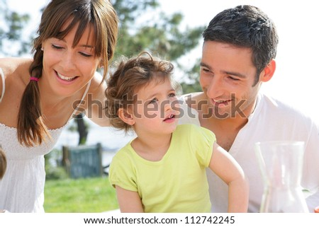 parents and their little girl having picnic in the park