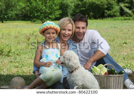 Parents and young daughter with dog and basket of vegetables
